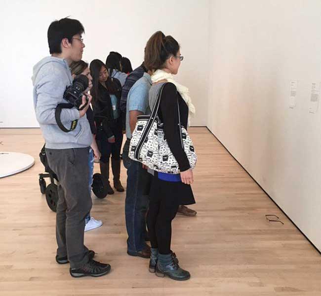 , Ils posent sur le Sol d'une Galerie des lunettes Lesquelles sont Prises pour des Oeuvres d'Art